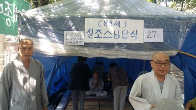 설조 스님의 단식 농성장인 천막에는 '88세 설조스님 단식'이라는 피켓이 부착돼 있다. 좌측에는 도정 스님, 우측에는 무위(현진) 스님의 모습이 보인다.