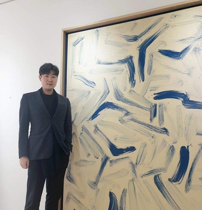 오는 25일 아트앤가이드를 통해 이우환 150호 '동풍' 공동구매 행사를 진행하는 김재욱 대표가 작품 앞에서 포즈를 취했다. (사진=열매컴퍼니 제공)